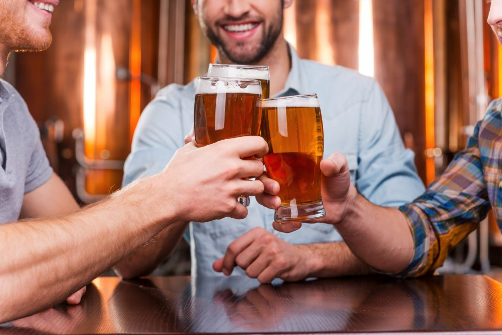 10674940-old-friends-meeting-close-up-of-three-happy-young-men-in-casual-wear-toasting-with-beer-while-sitting-in-beer-pub-together
